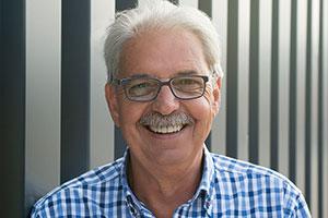 Günther Kamps hat kurze graue Haare, einen Schnauzer in dunklerem Grau und trägt eine Brille mit schwarzem Gestell.