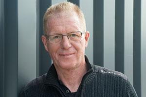 Ralf Willems hat kurze, rot-blonde Haare und trägt eine Brille.