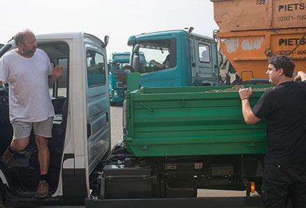 Auf dem Wertstoffhof steigt ein Mann mit weißem Shirt aus dem Führerhaus des Transporters mit Ladefläche. Ein weiterer steht an der Ladefläche des Transporters.