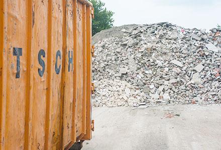 Ein orangefarbener Container steht vor einem Abfallberg mit Bauschutt